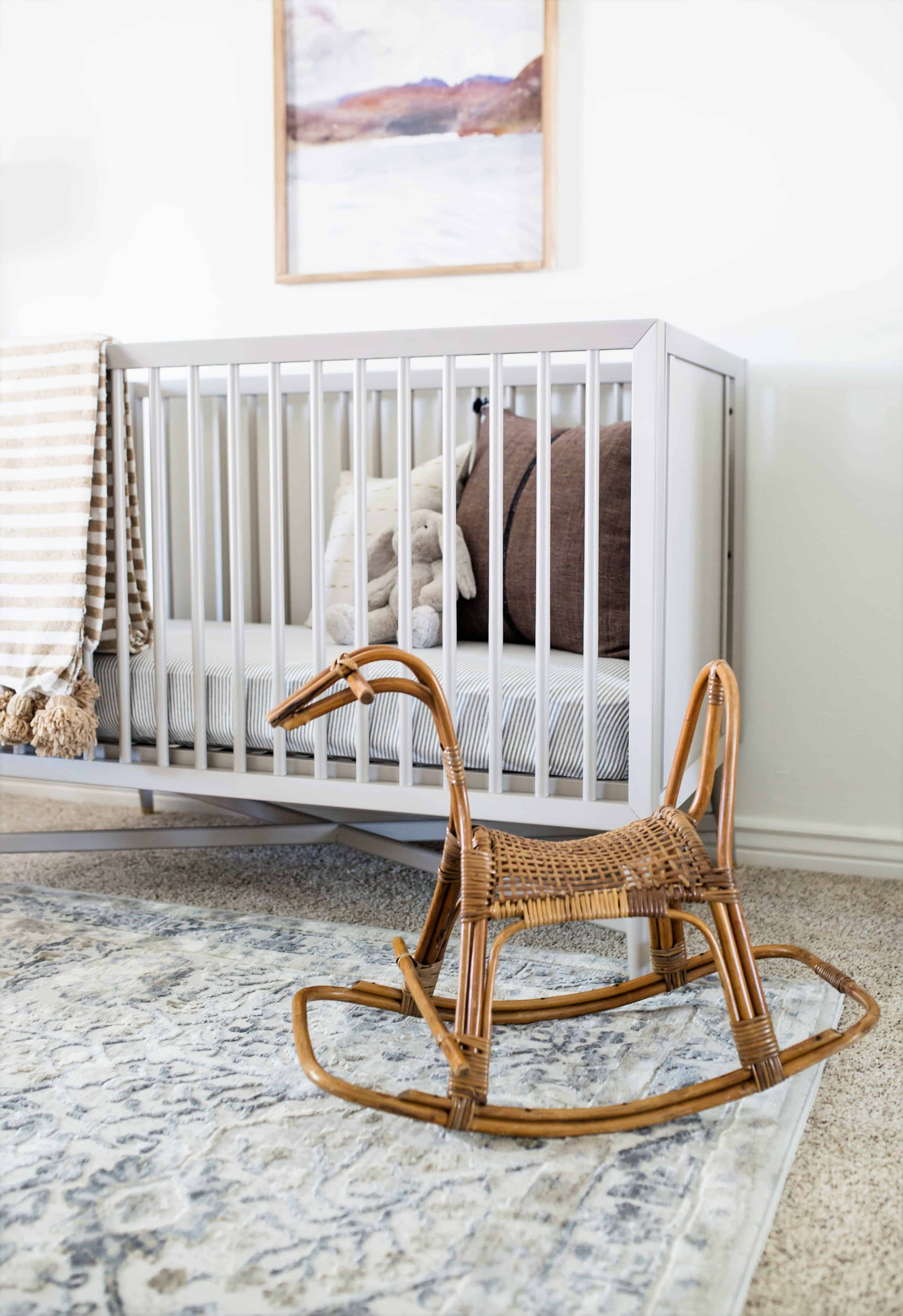 vintage rattan rocking horse in front of gray modern minimal crib
