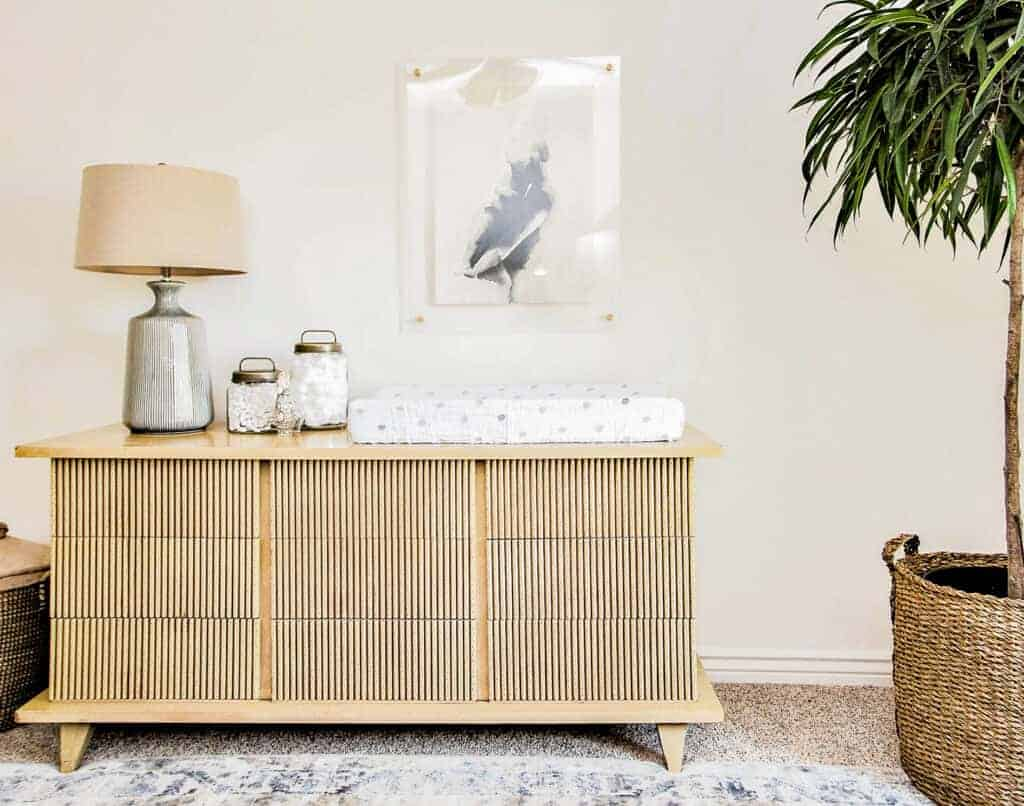 minimal vintage fluted dresser with blue lamp on the left and black and white art in acrylic frame above