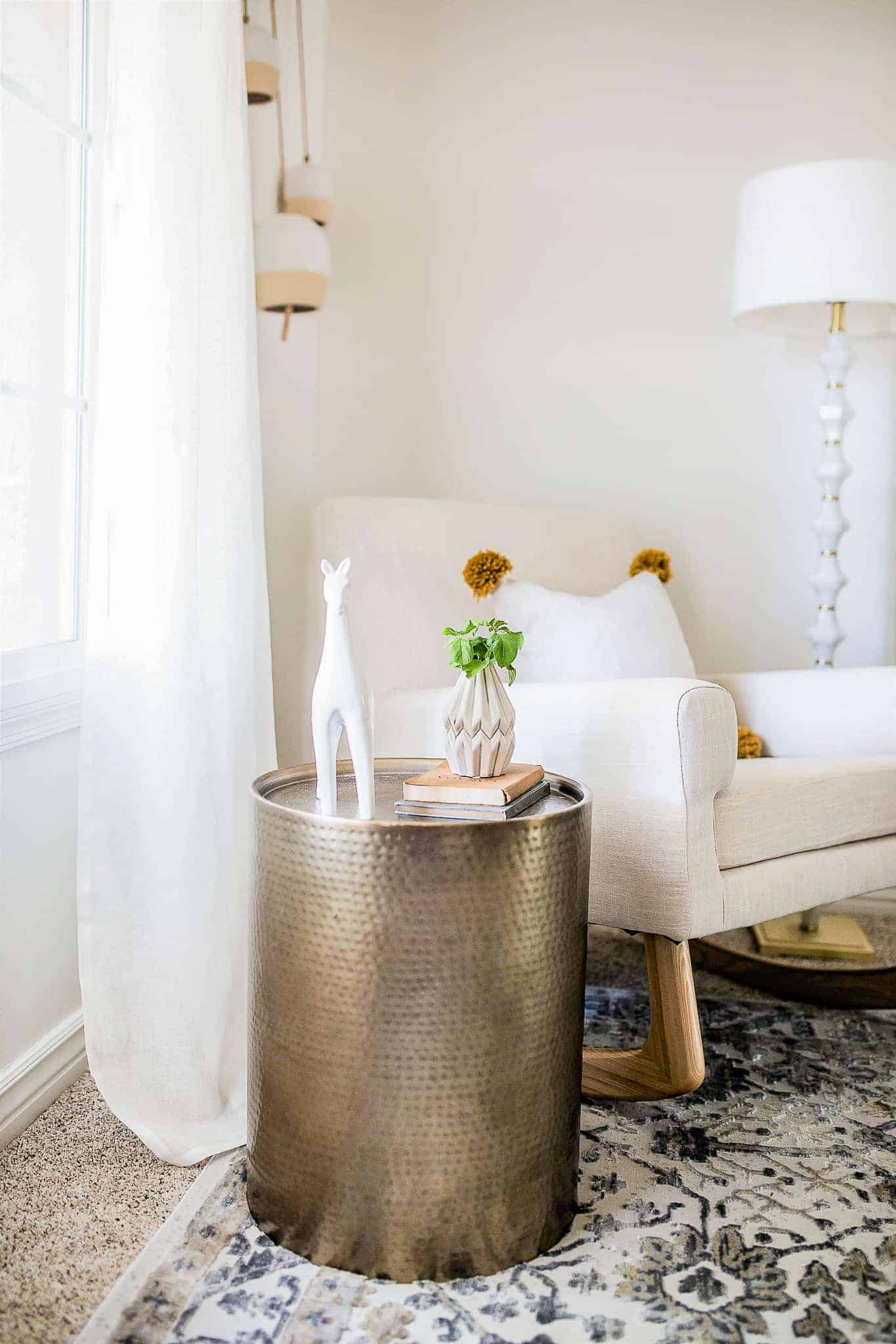 round metal side table next to an upholstered rocking chair with pom pom pillow