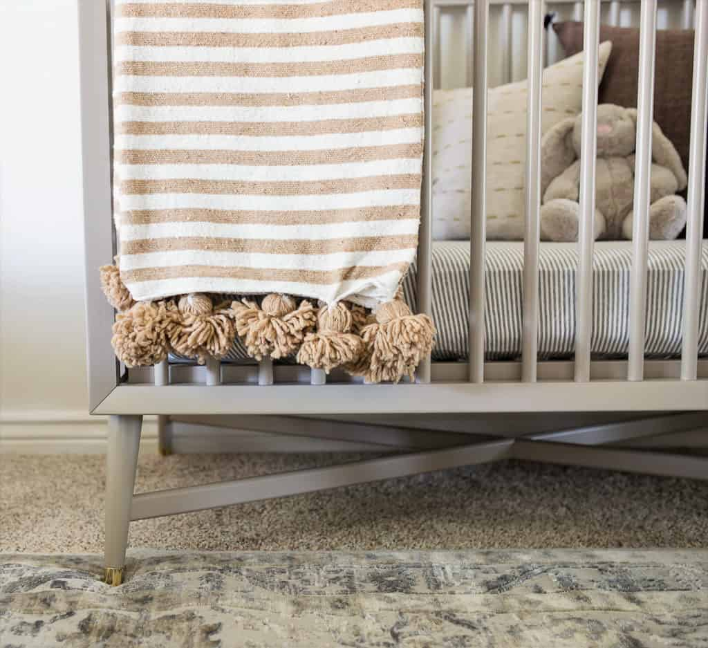 yellow striped pom pom blanket draped over gray crib in minimal nursery designed with heart