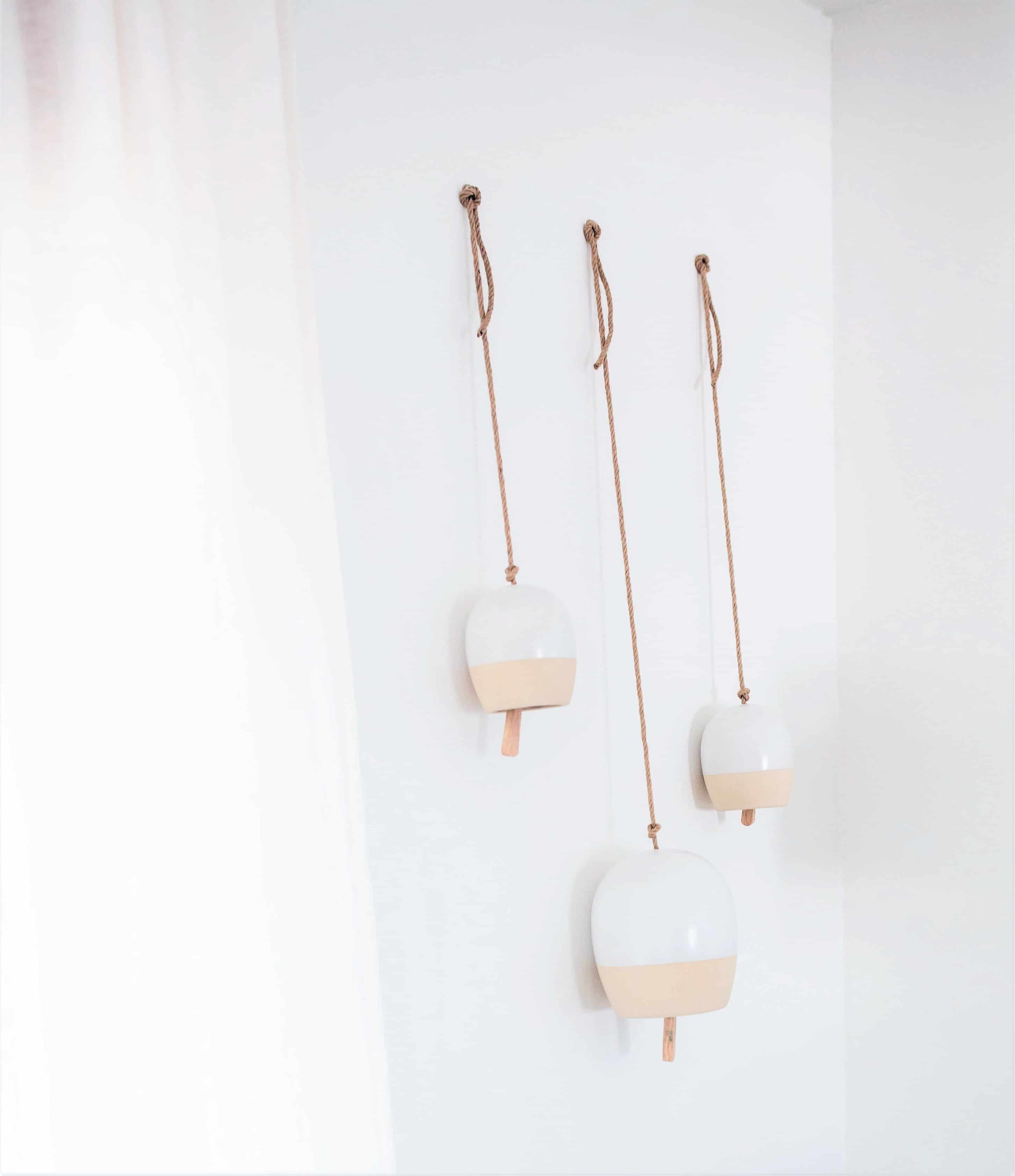 three white minimal ceramic two-tone bells hanging on a white wall