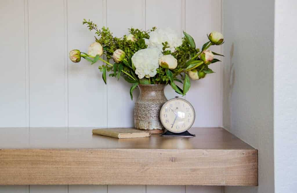 close up shot of floating desk and vase of flowers and clock