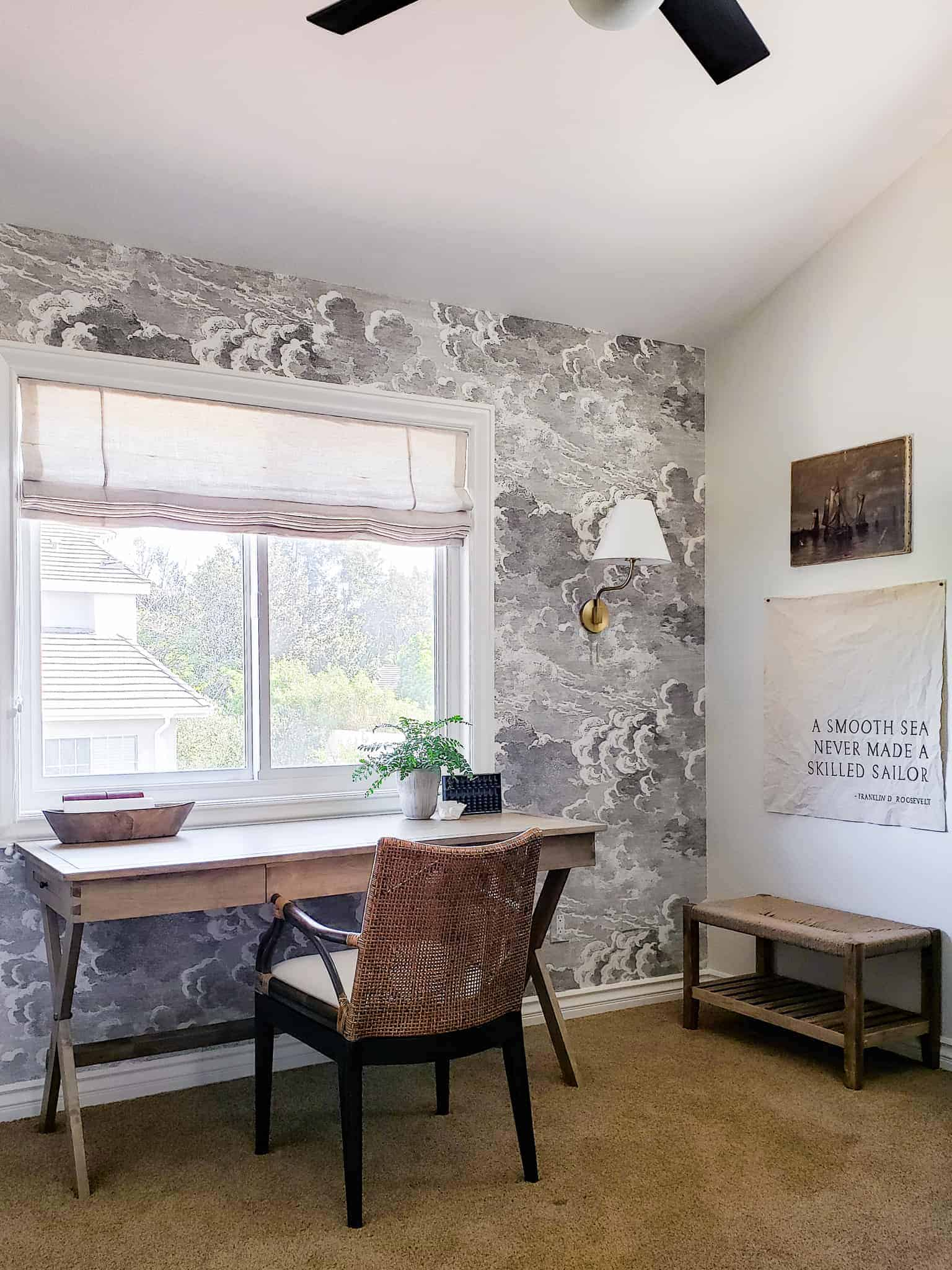 desk and chair in front of storm cloud wallpaper and window with shade