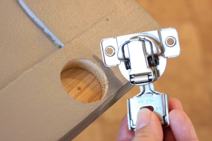 picture of a cabinet drilled for hidden hinges and a hand holding a hinge