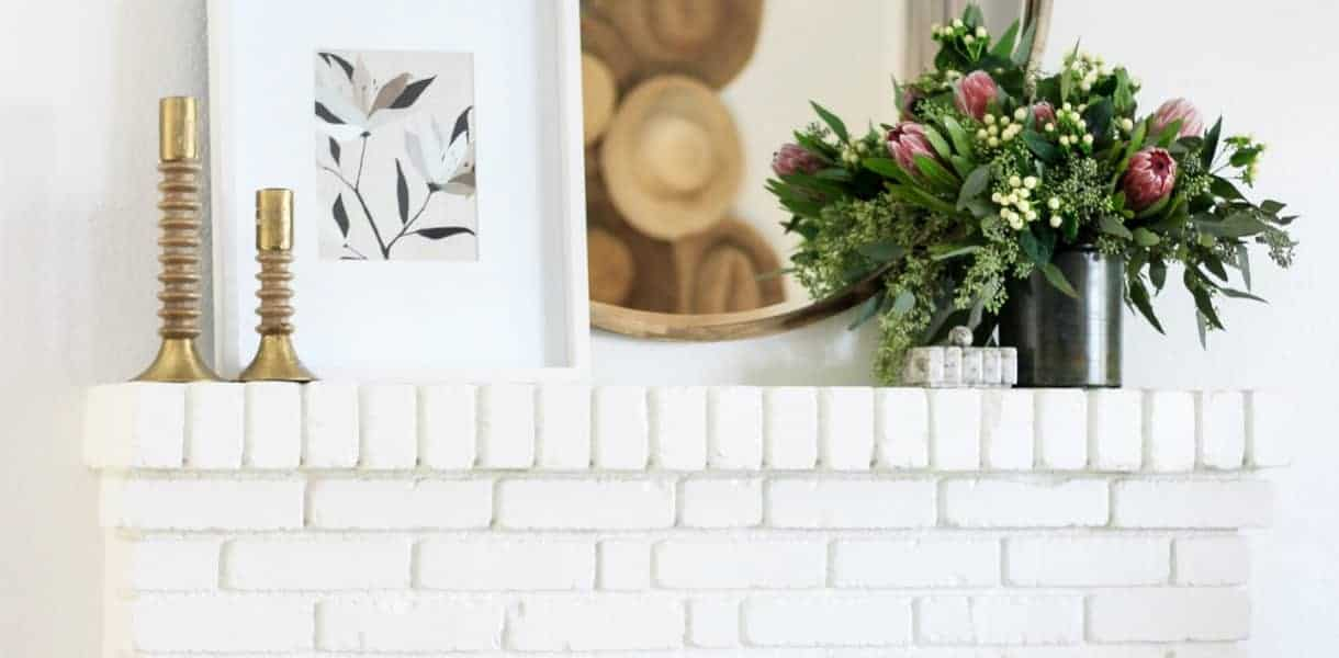 white brick fireplace with round mirror above