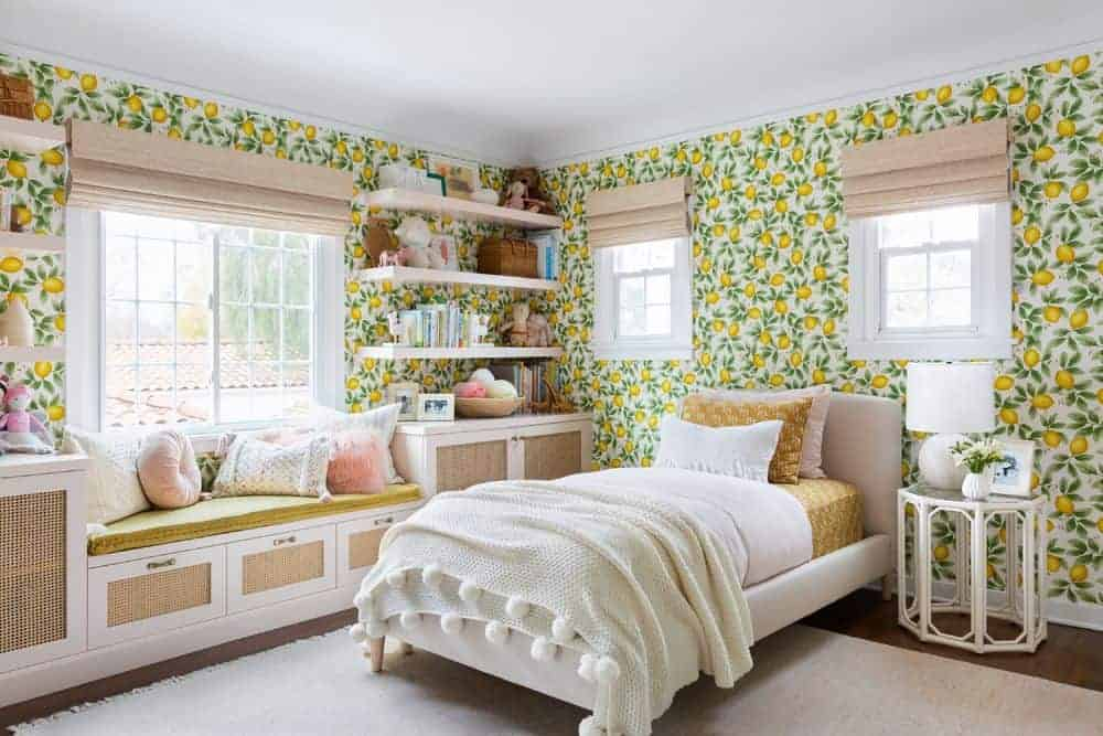 girls bedroom with lemon wallpaper, window seat and shelves, and twin bed