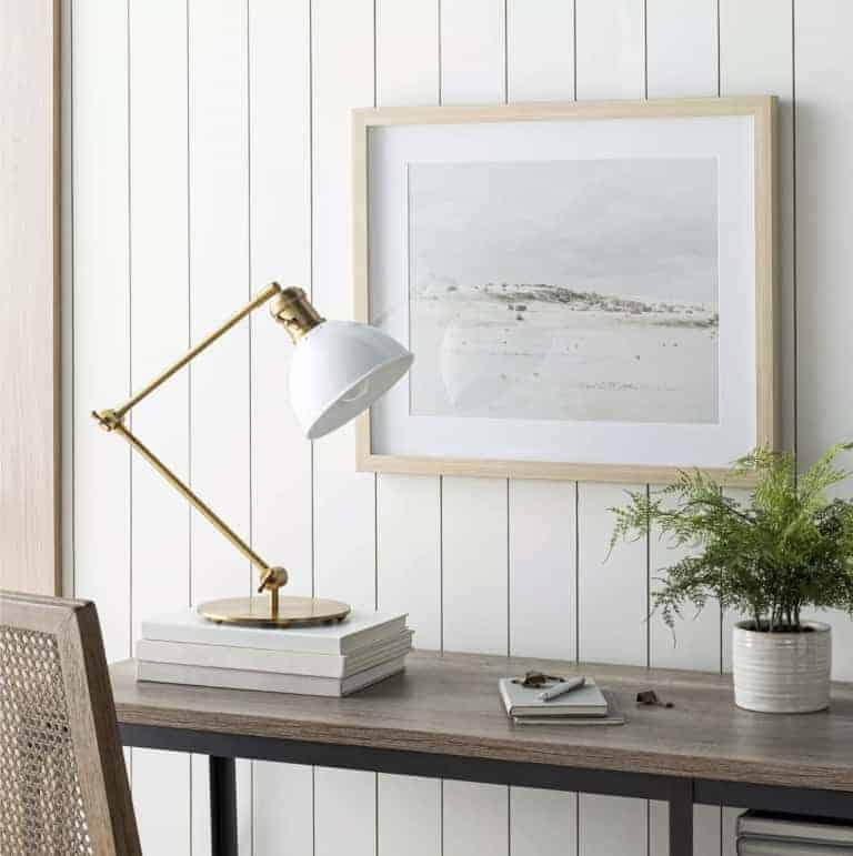 white and gold task lamp on top of some books on a console table