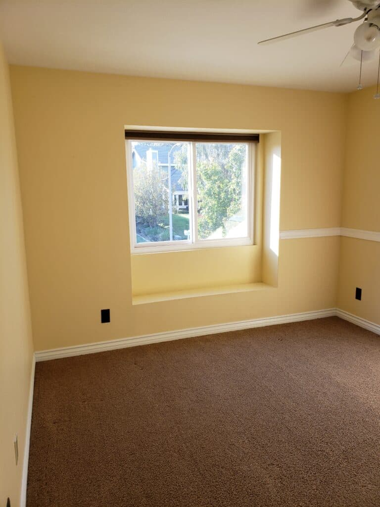 Bedroom With Yellow Walls and Window