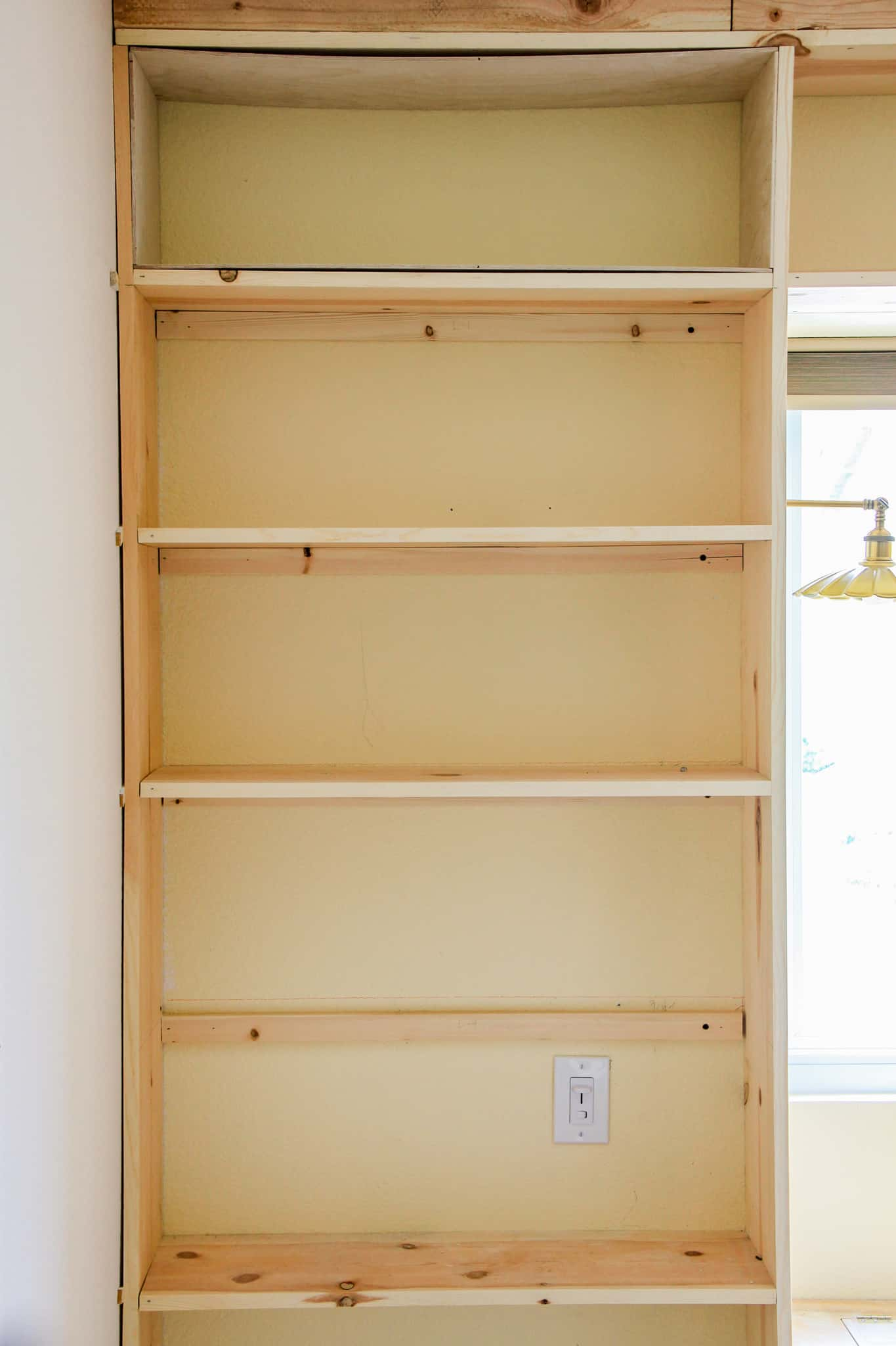 pine built-in shelves against yellow wall