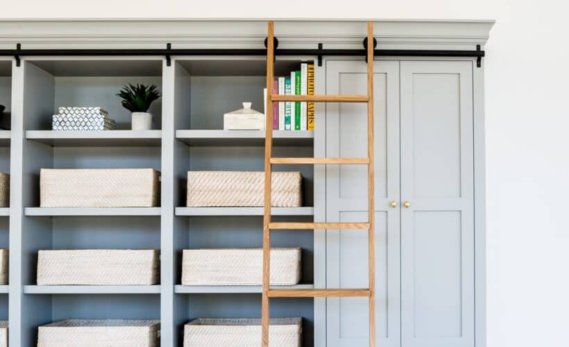 blue built in shelving unit with library ladder
