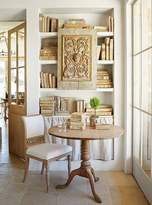 small table with chair in front of a bookcase full of books