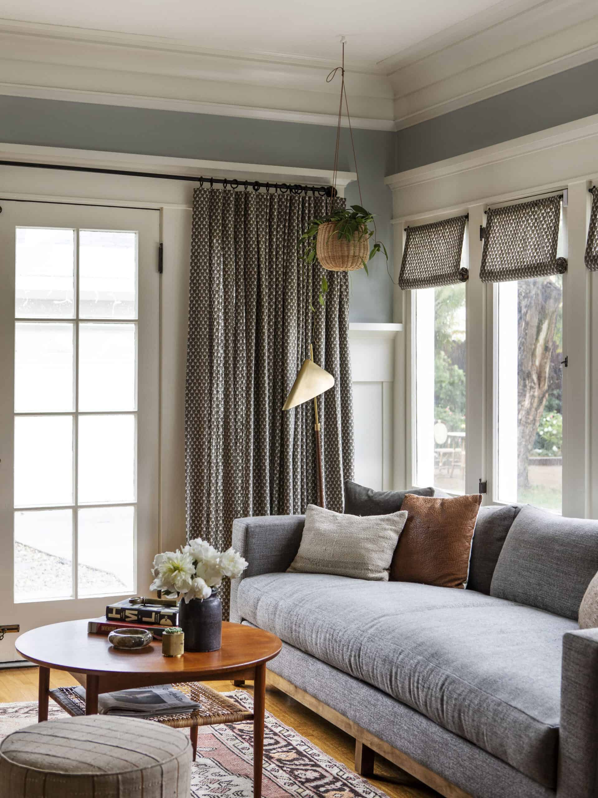 Corner of living room with brown curtains and roman shades, blue couch, and hanging plant