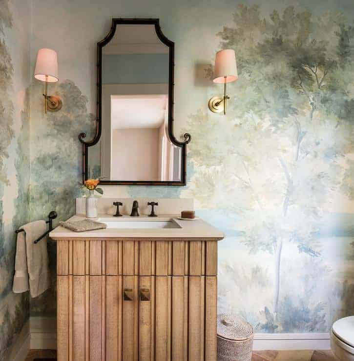 powder room with hand painted trees, wood vanity, two sconces, and unique mirror