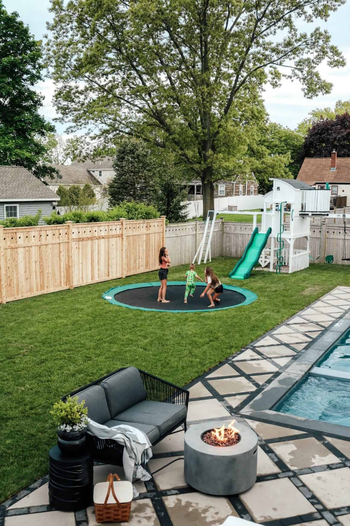 backyard with in ground trampoline next to a pool