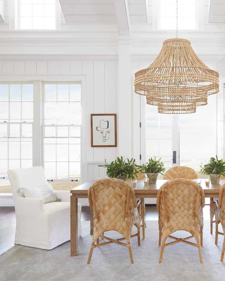 Dining room with large rattan chandelier, woven chairs, upholstered head chair, white vertical shiplap walls, lots of windows