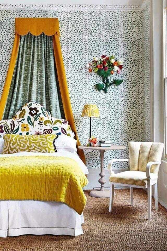 upholstered bed with yellow blanket and yellow and blue bed canopy with chair and wallpaper