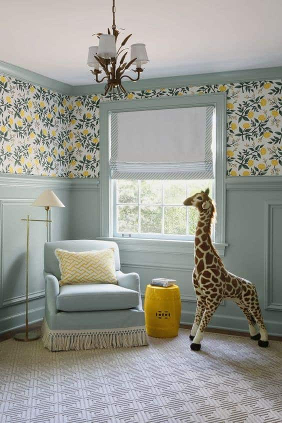 nursery with blue wainscoating, yellow and green floral wallpaper, a chair in front of a window and a large giraffe stuffed animal