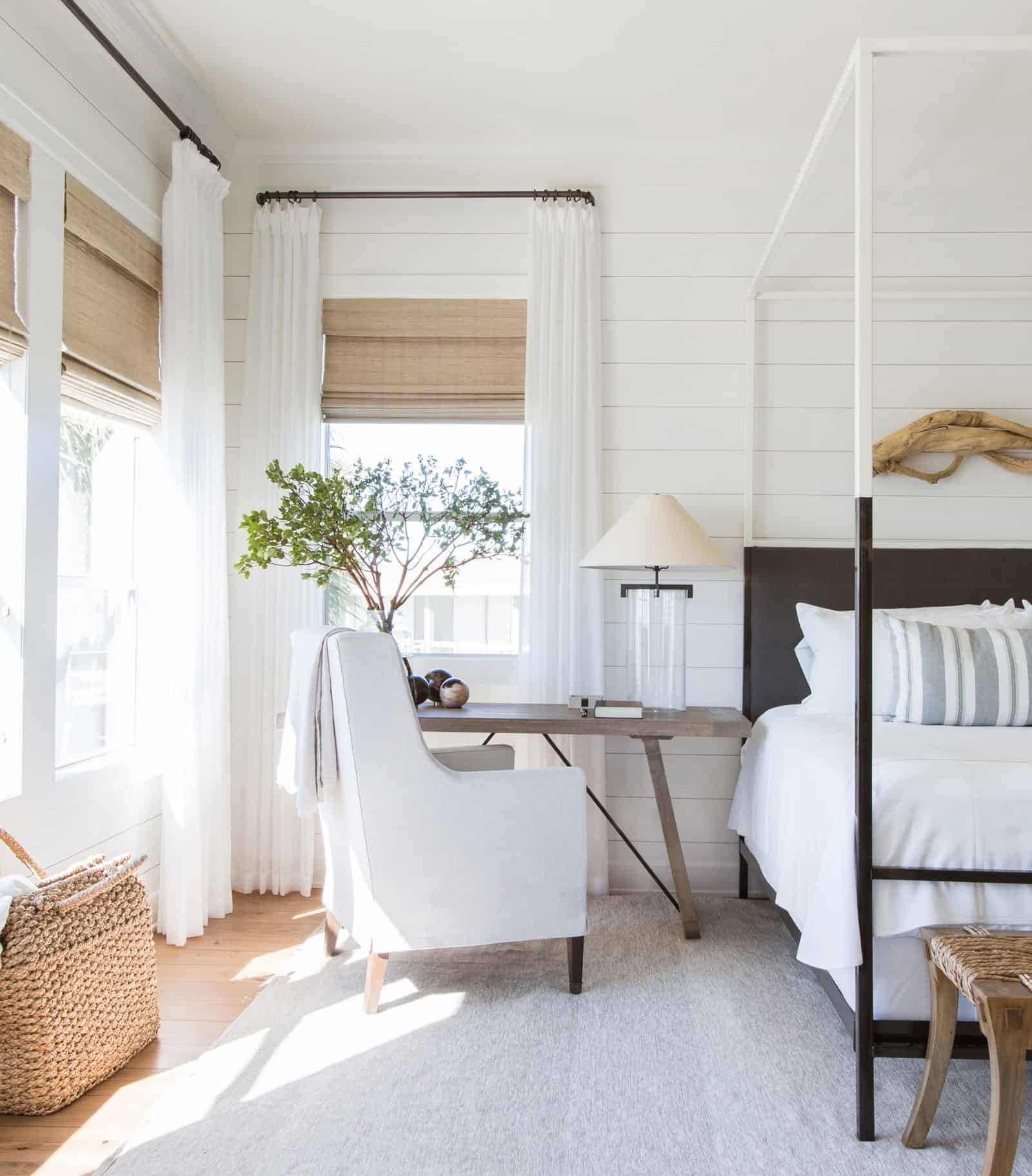 beach house bedroom with canopy bed and gray desk table beside bed with upholstered chair