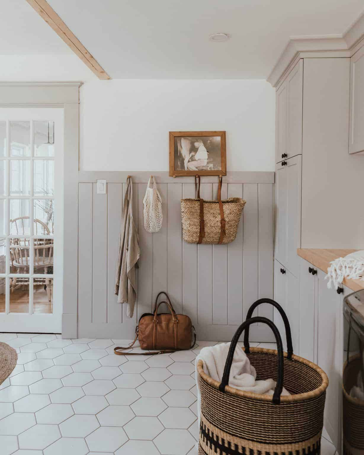 neutral laundry room with vertical shiplap wainscoting and straw bag