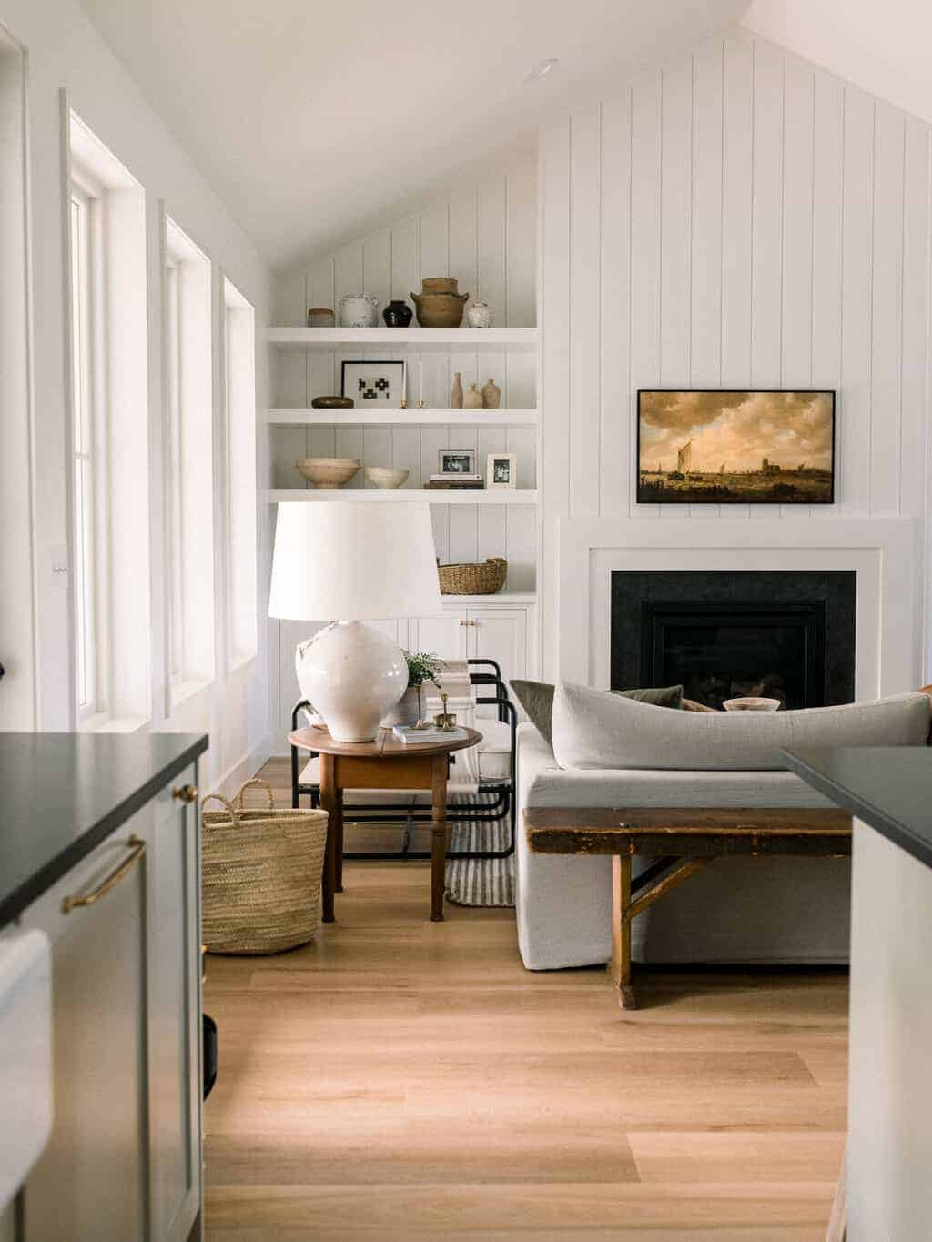 Living room with white vertical shiplap and frame tv above fireplace