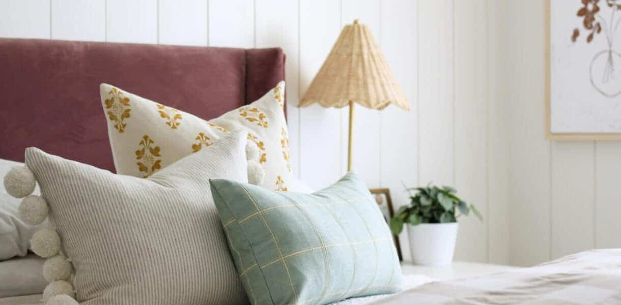 three different throw pillows on berry velvet headboard bed