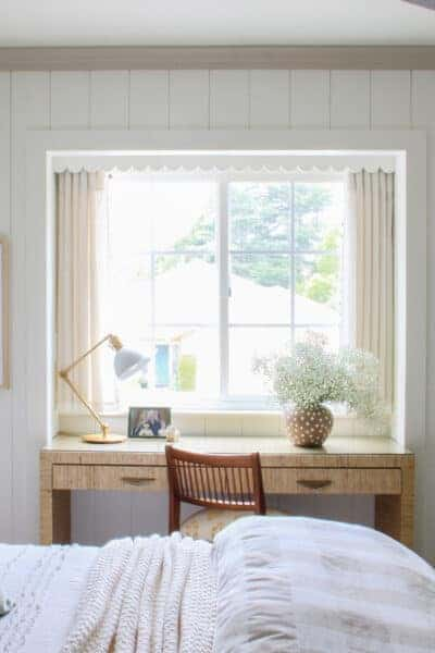 teen bedroom with white vertical shiplap walls, window centered, stacked art on either side