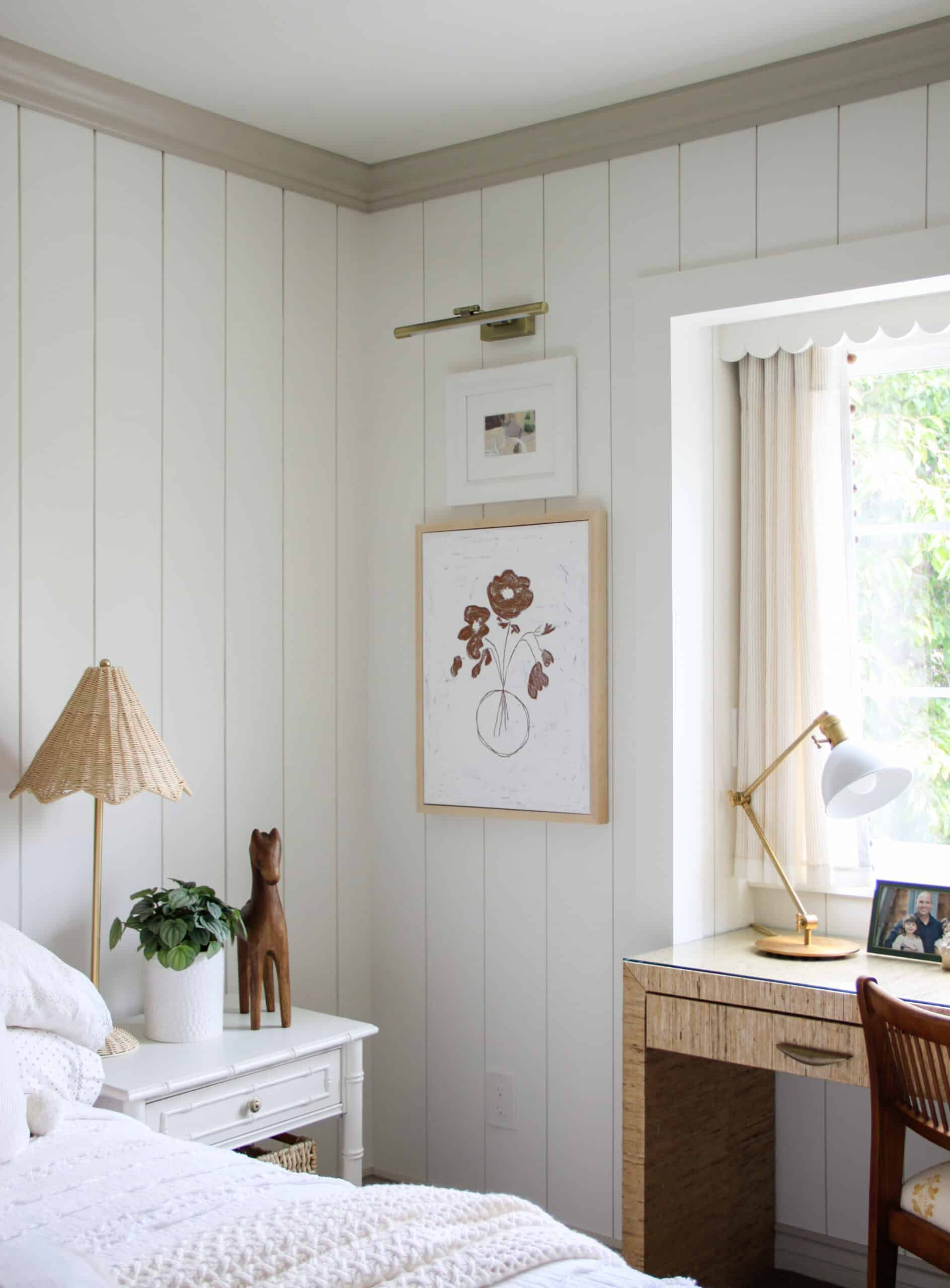 corner of shiplap teen girl bedroom with stacked art, rattan lamp, and grasscloth desk