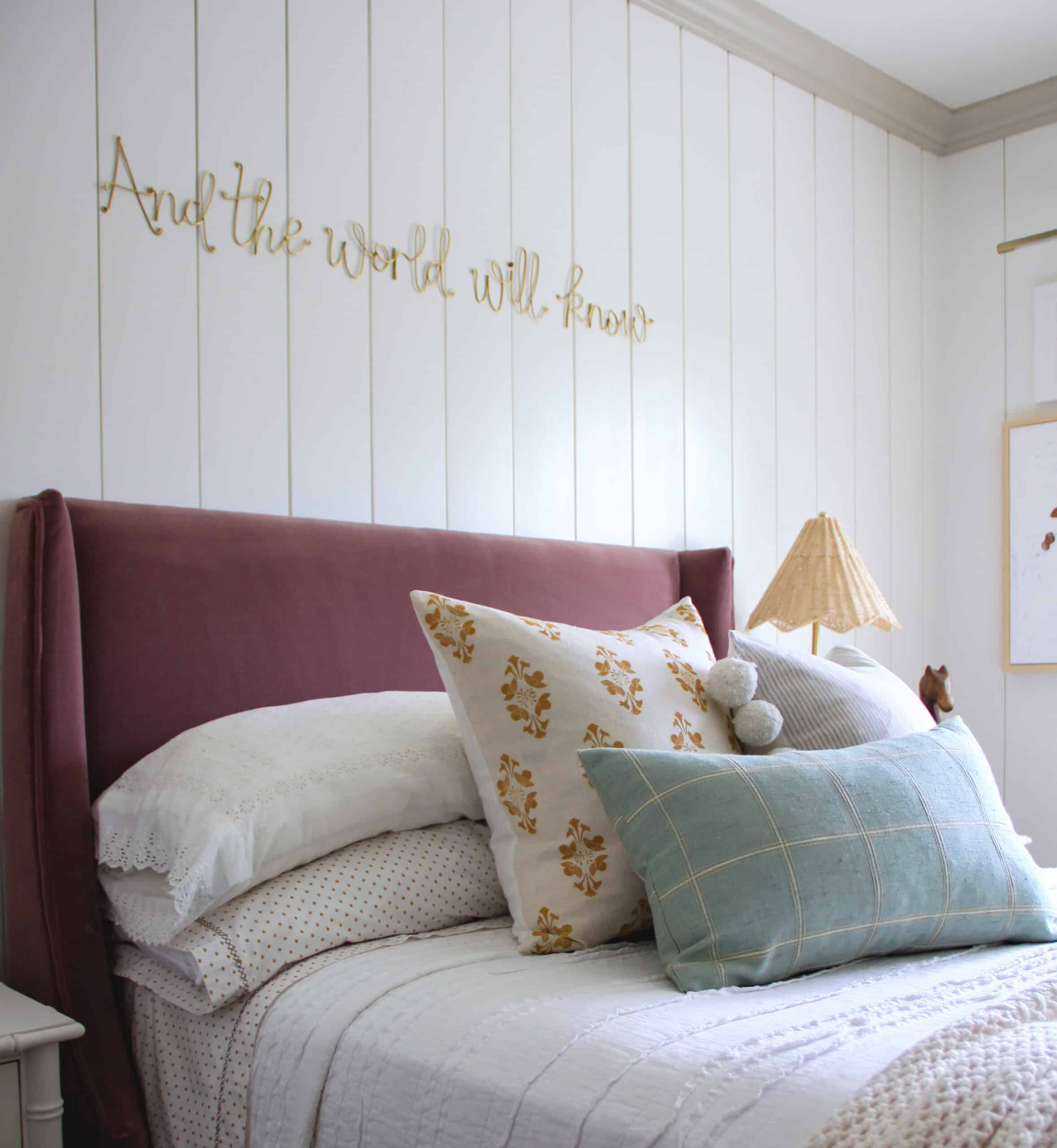 three different colored throw pillows on berry velvet headboard bed