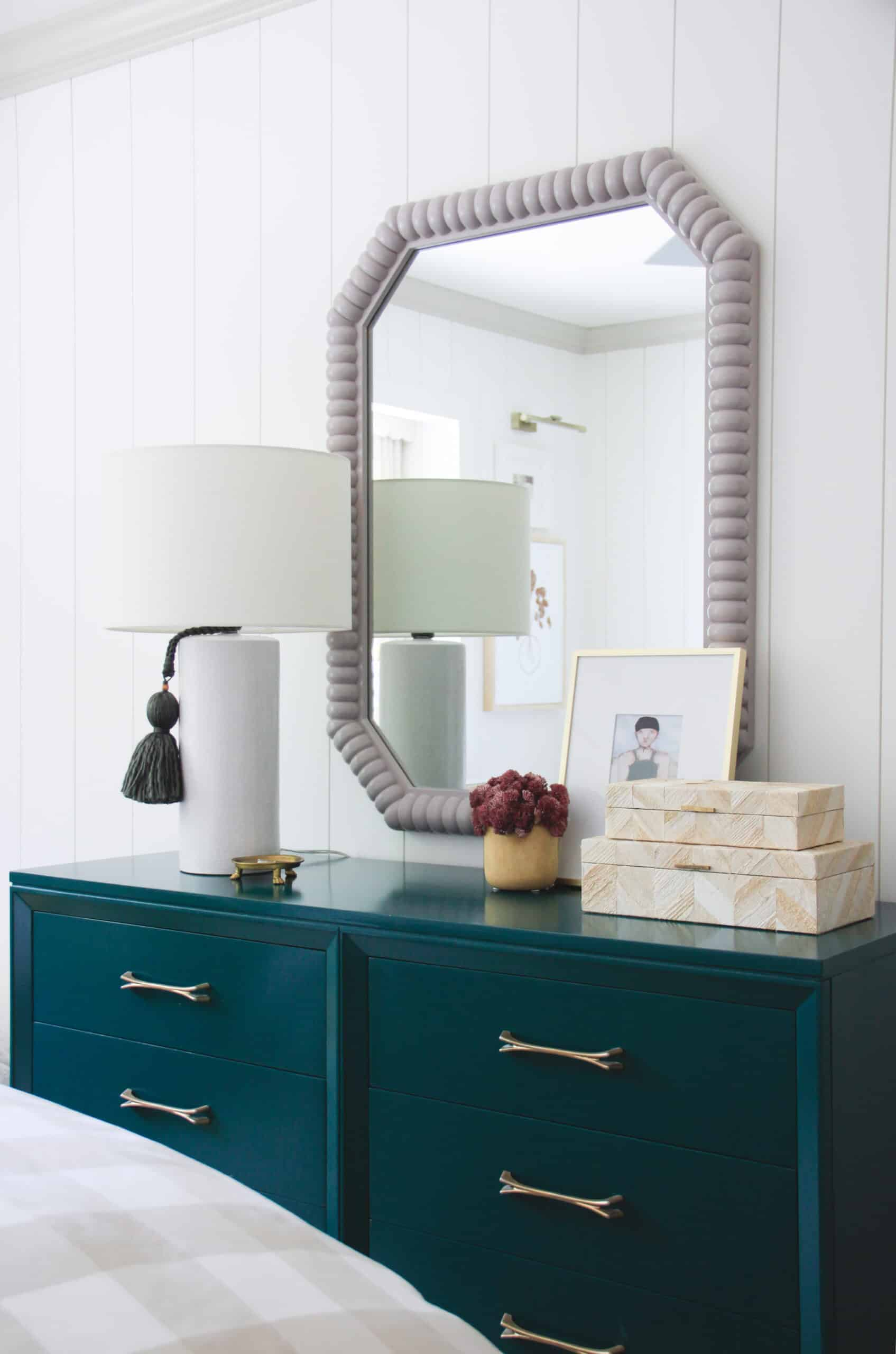 dark green dresser with white lamp and lavender mirror in teen bedroom