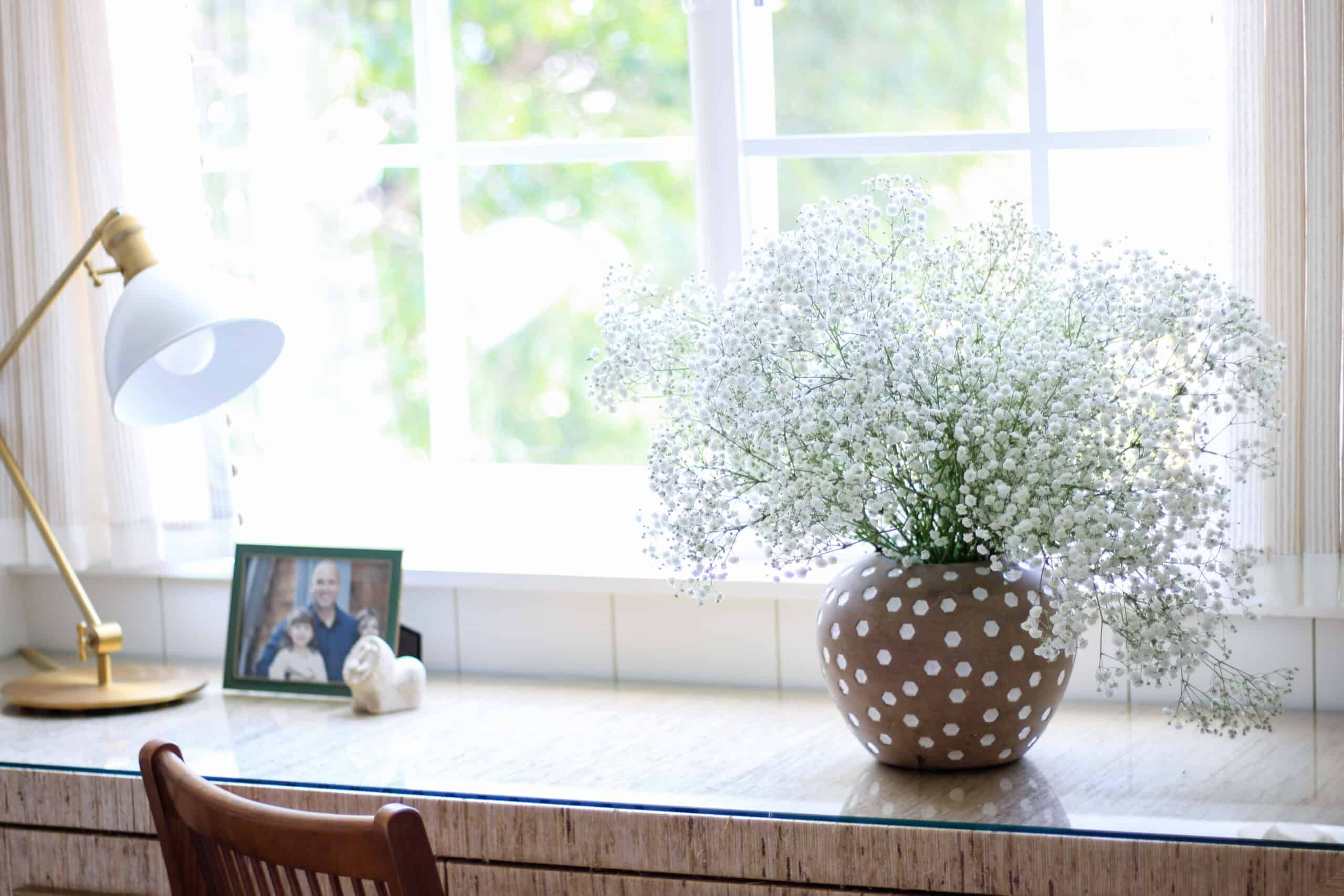 glass topped desk with vase of baby's breath