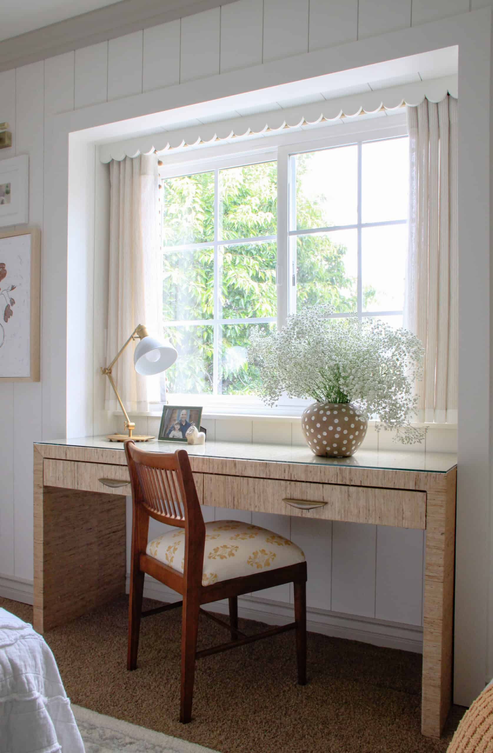 grasscloth desk with vintage chair in front of window with baby's breath in a vase