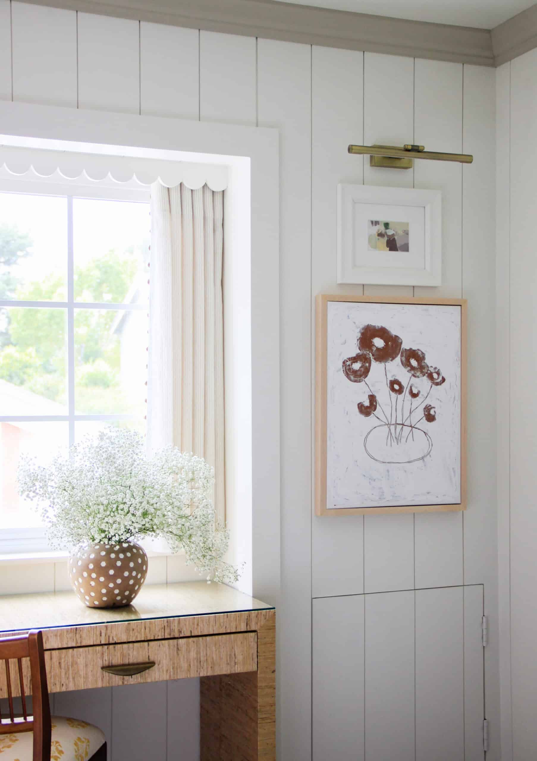 corner of shiplap bedroom with stacked art and baby's breath in a vase