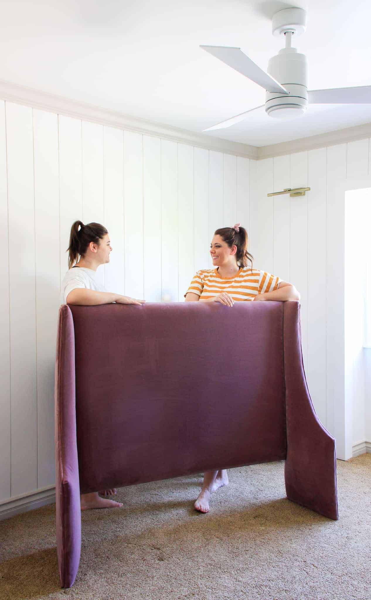 mother and daughter standing behind berry velvet upholstered headboard