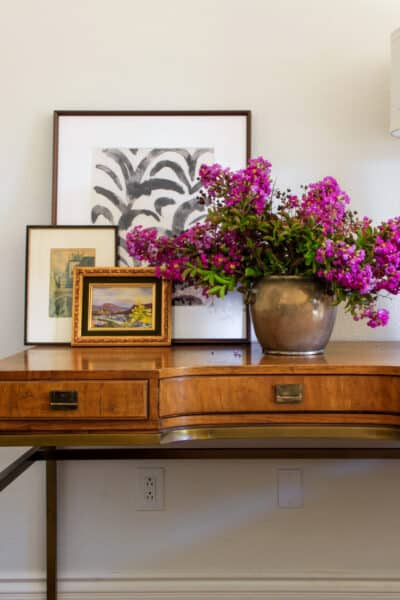 vintage wood and brass desk with brass vase full of lilacs