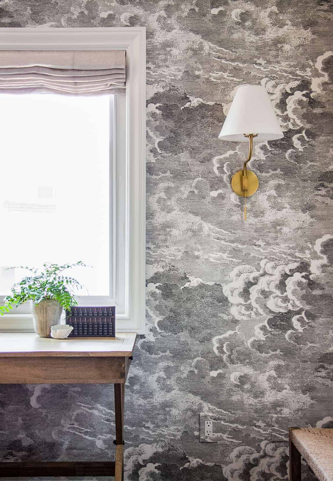 black and white storm cloud wallpaper with brass sconce and wooden desk