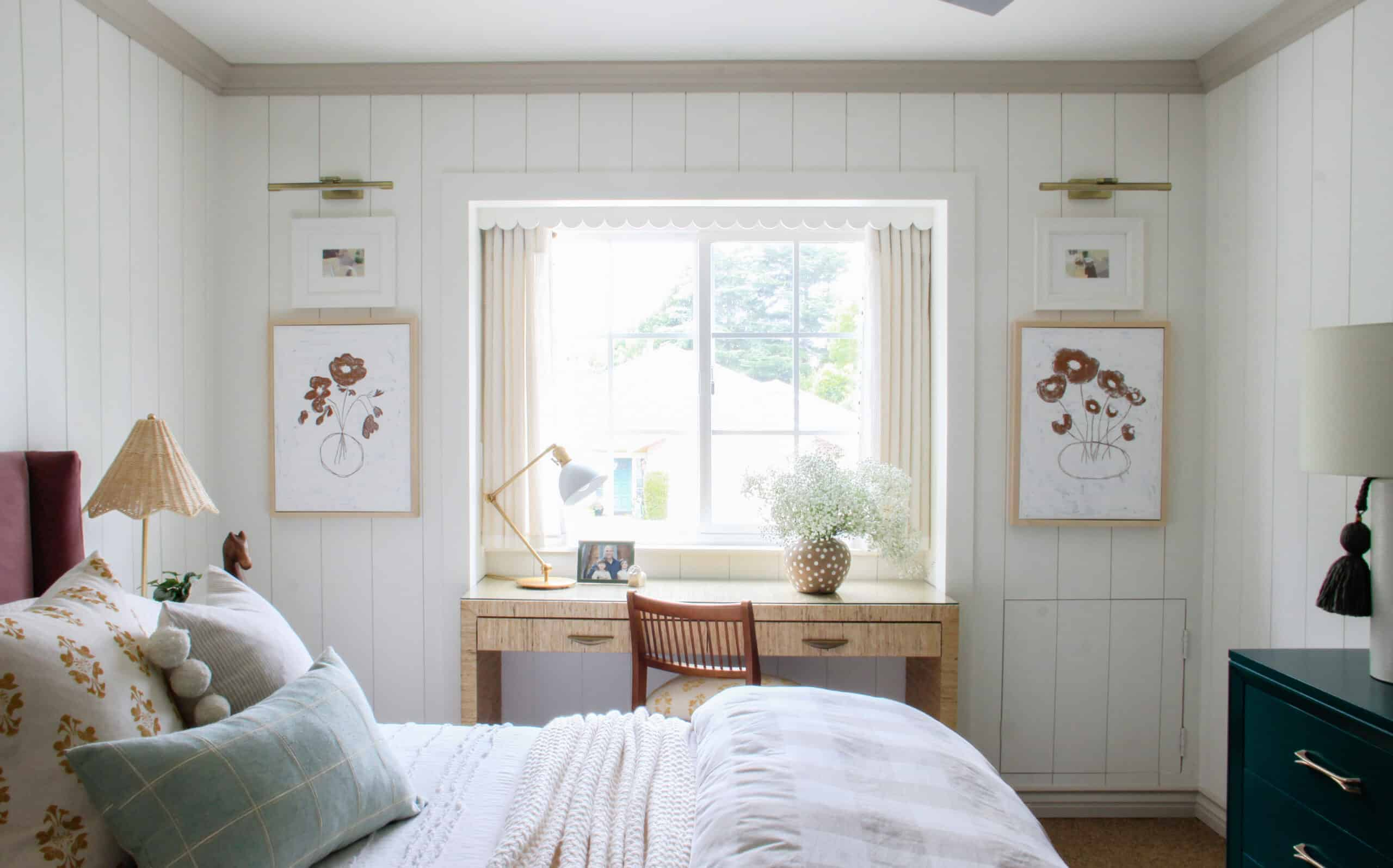 bedroom with white vertical shiplap, window with desk in front of it
