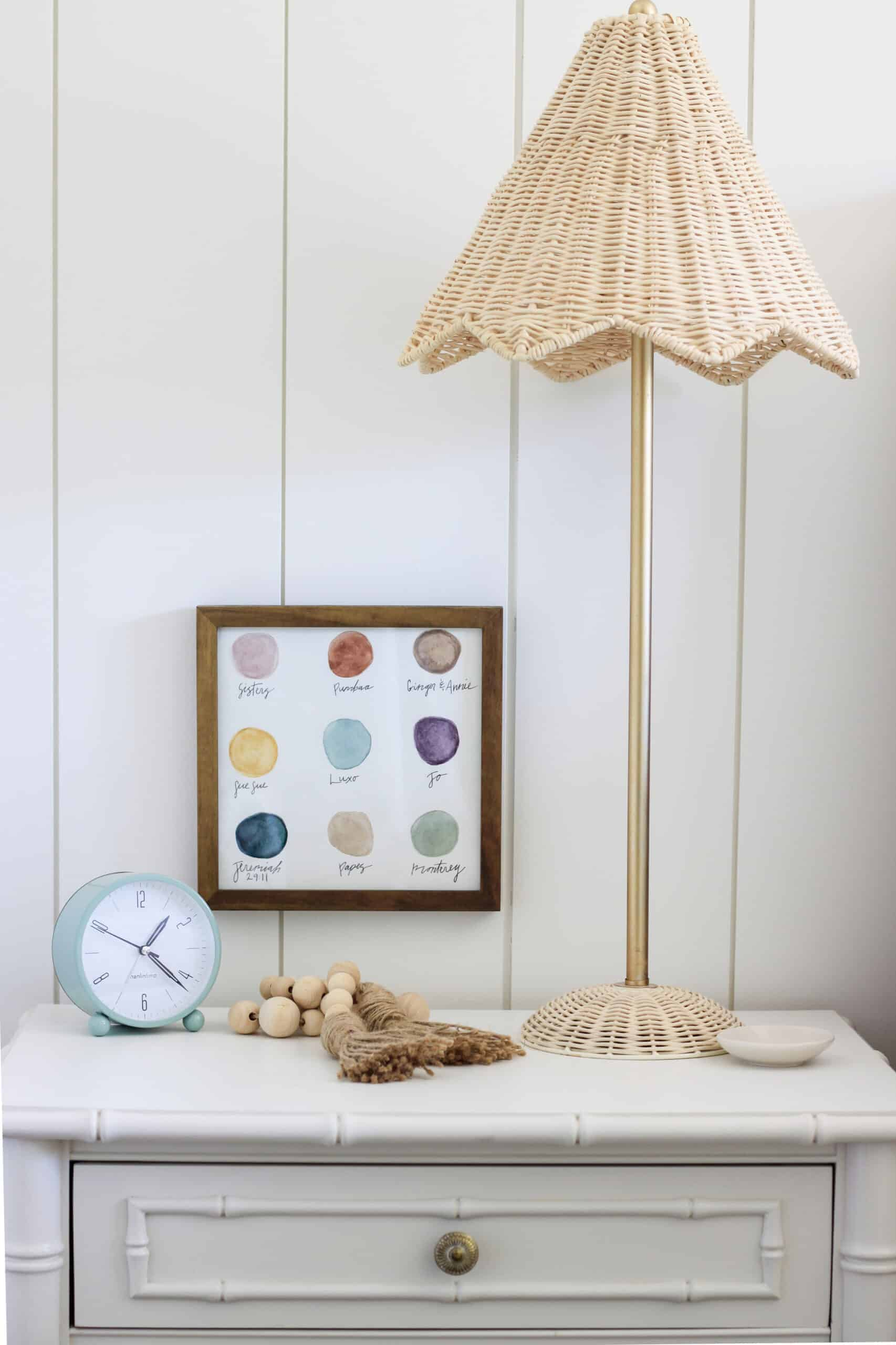 rattan parasol lamp on a white nightstand, watercolor dot artwork and mint alarm clock
