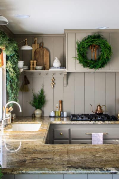 taupe shiplap kitchen with green wreath on hood