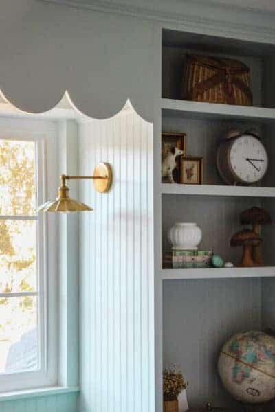 blue built ins with gold sconce