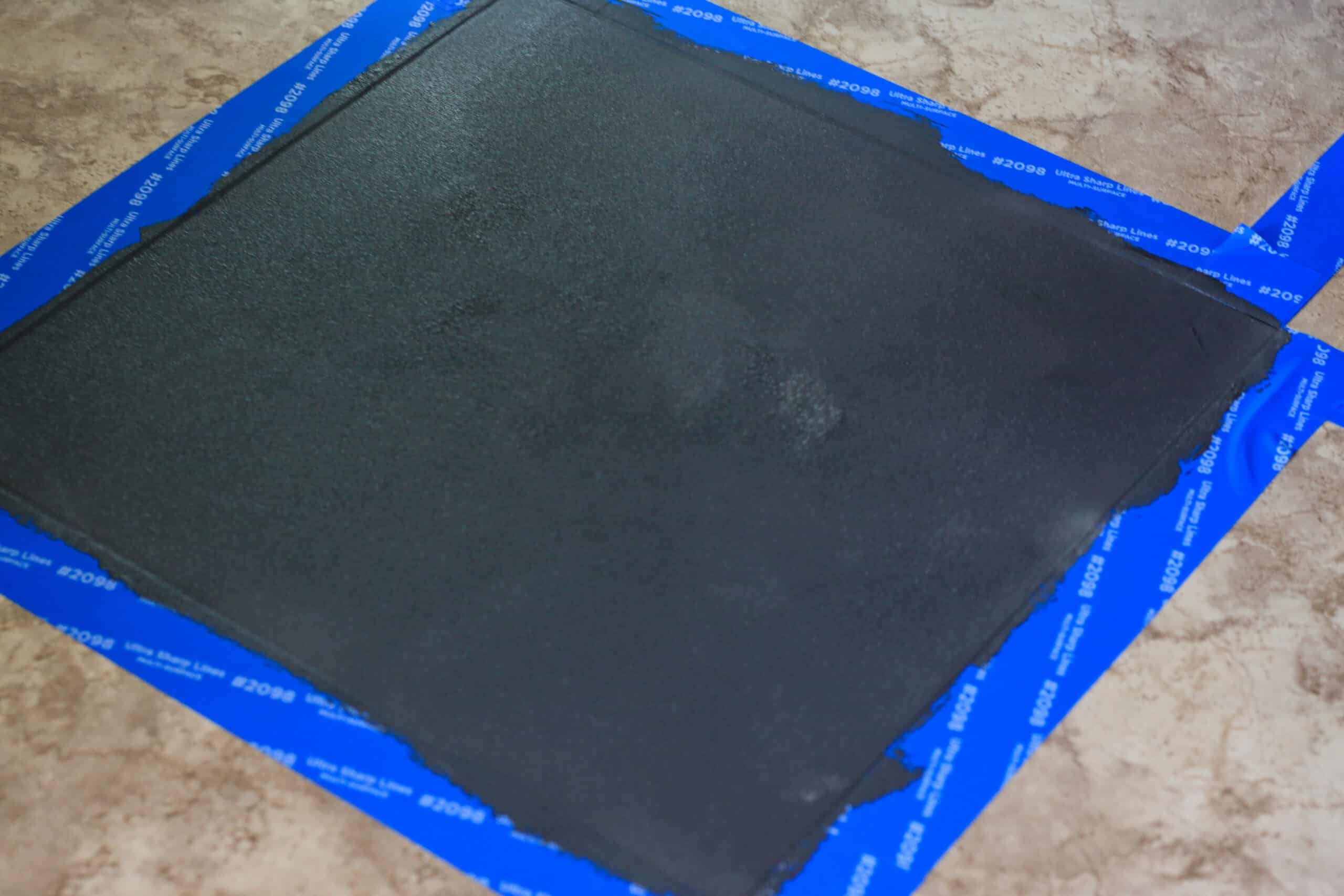 black painted tile with blue painters tape