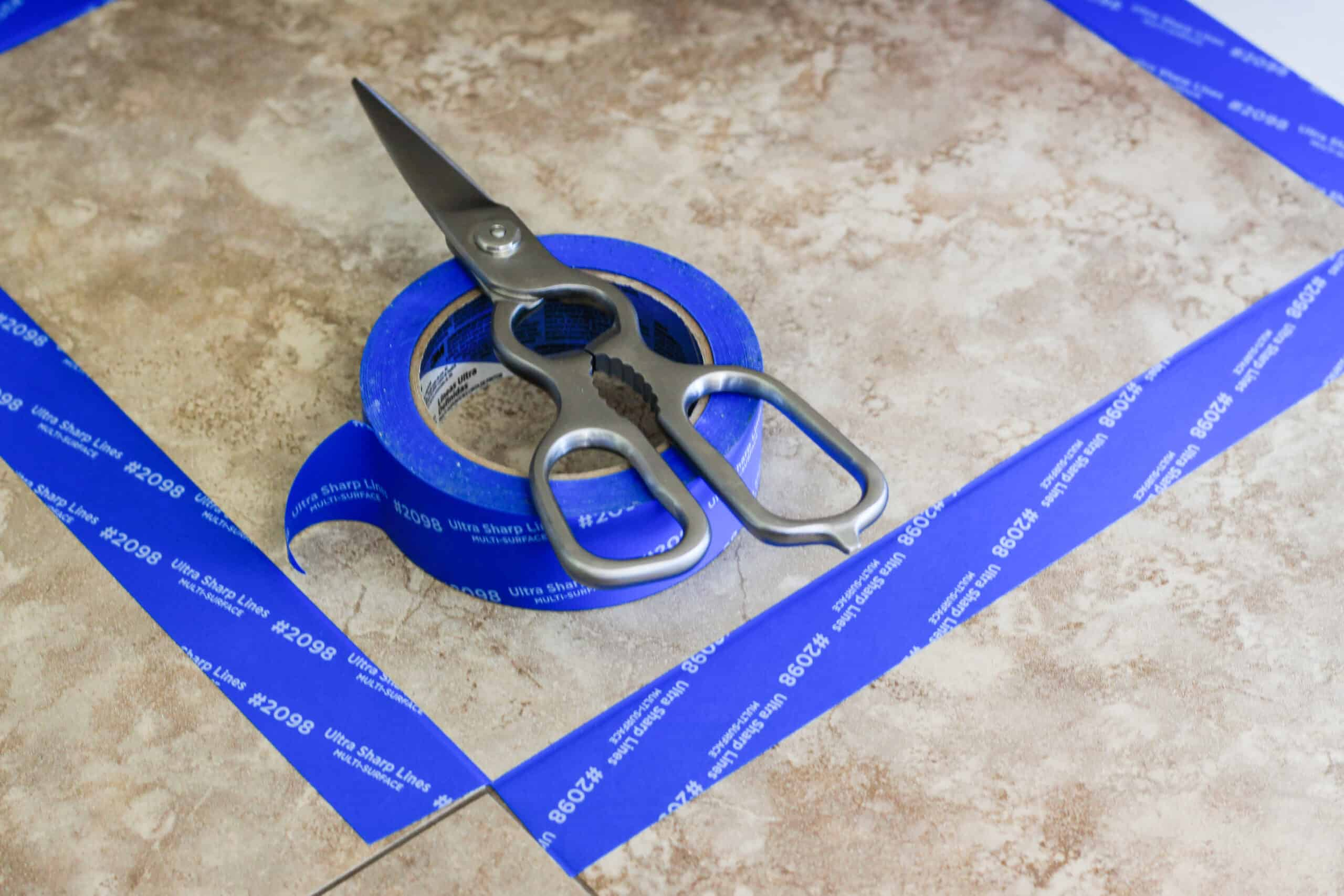 brown tile floors with blue painters tape and scissors