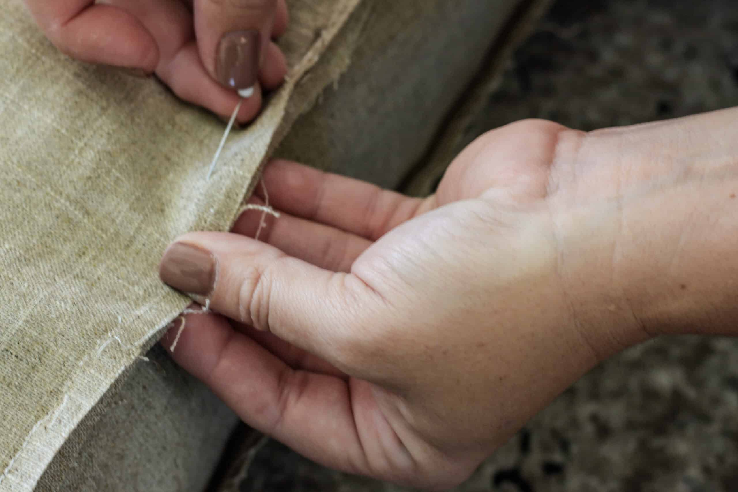 hands pinning brown fabric