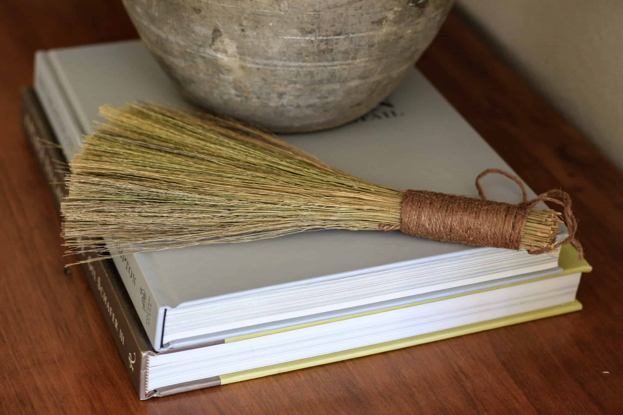 antique hand broom on stack of books
