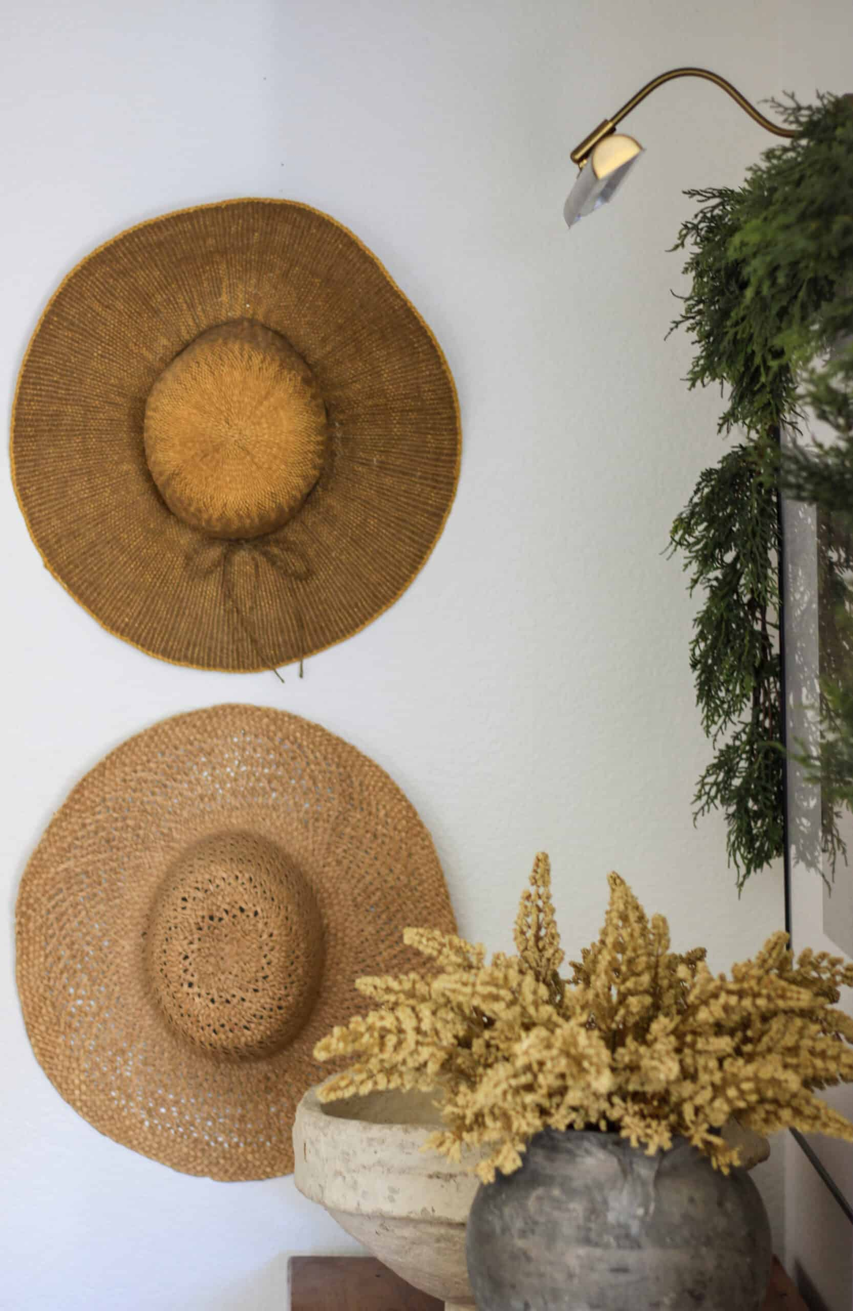 close up of hats on wall and vase of ochre stems