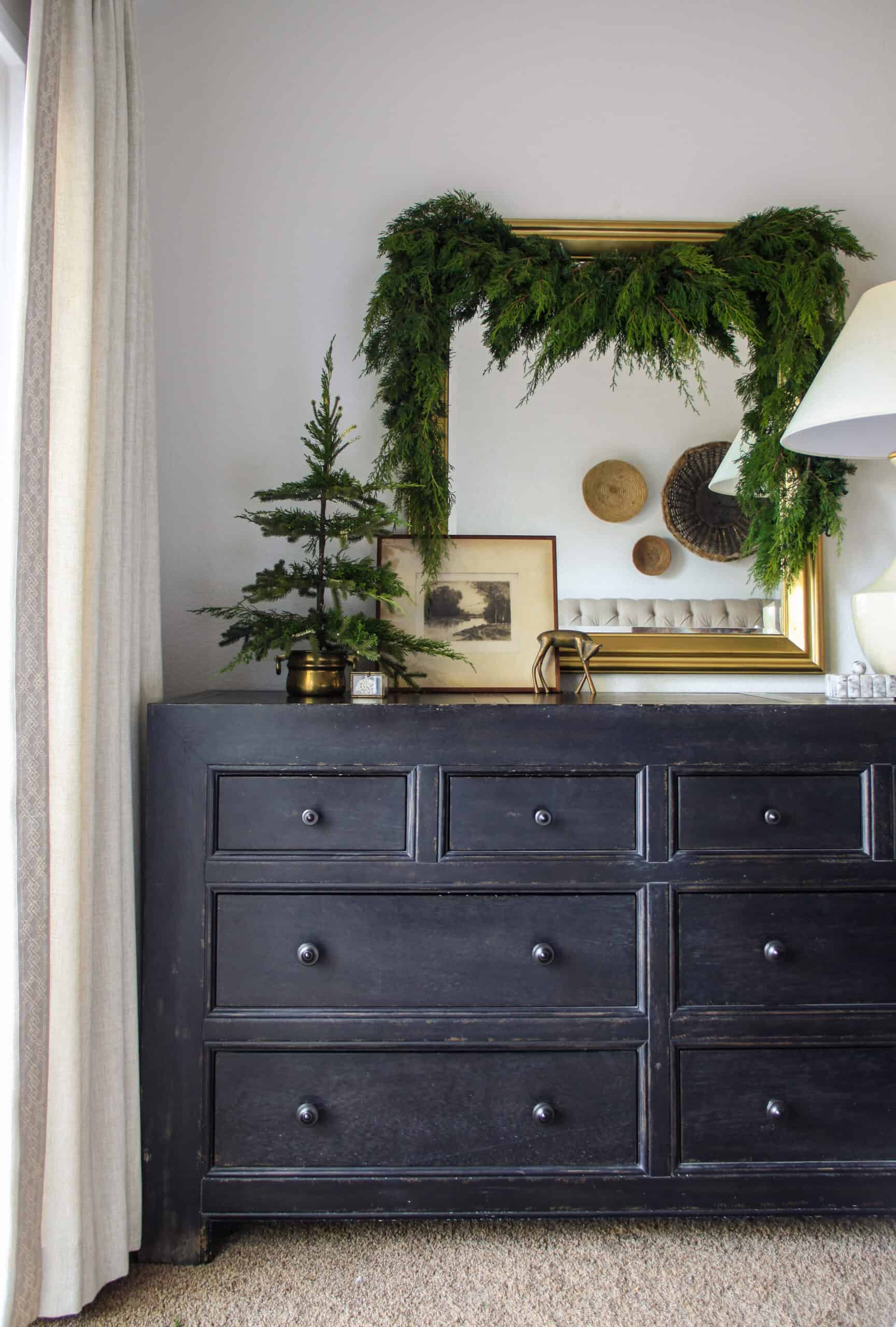 Black dresser with gold mirror and garland above
