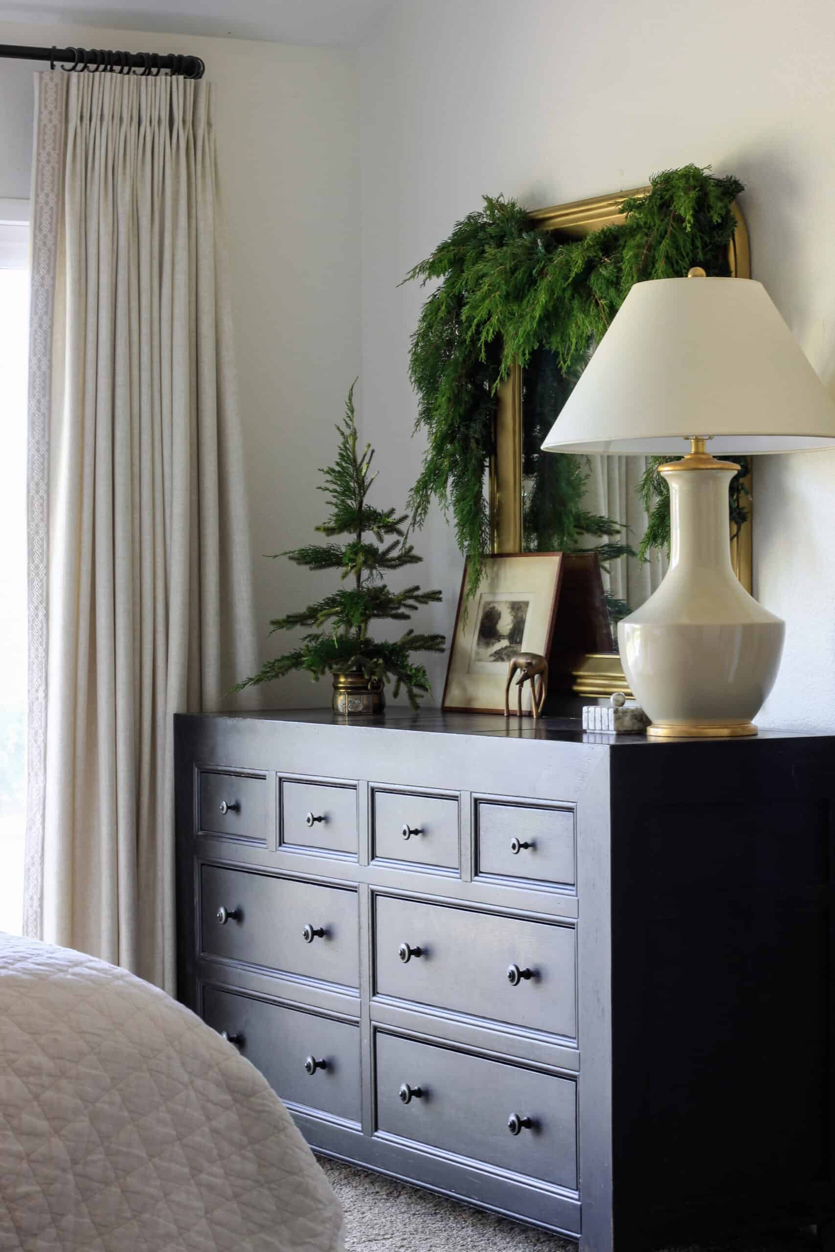 Black dresser with lamp and round mirror