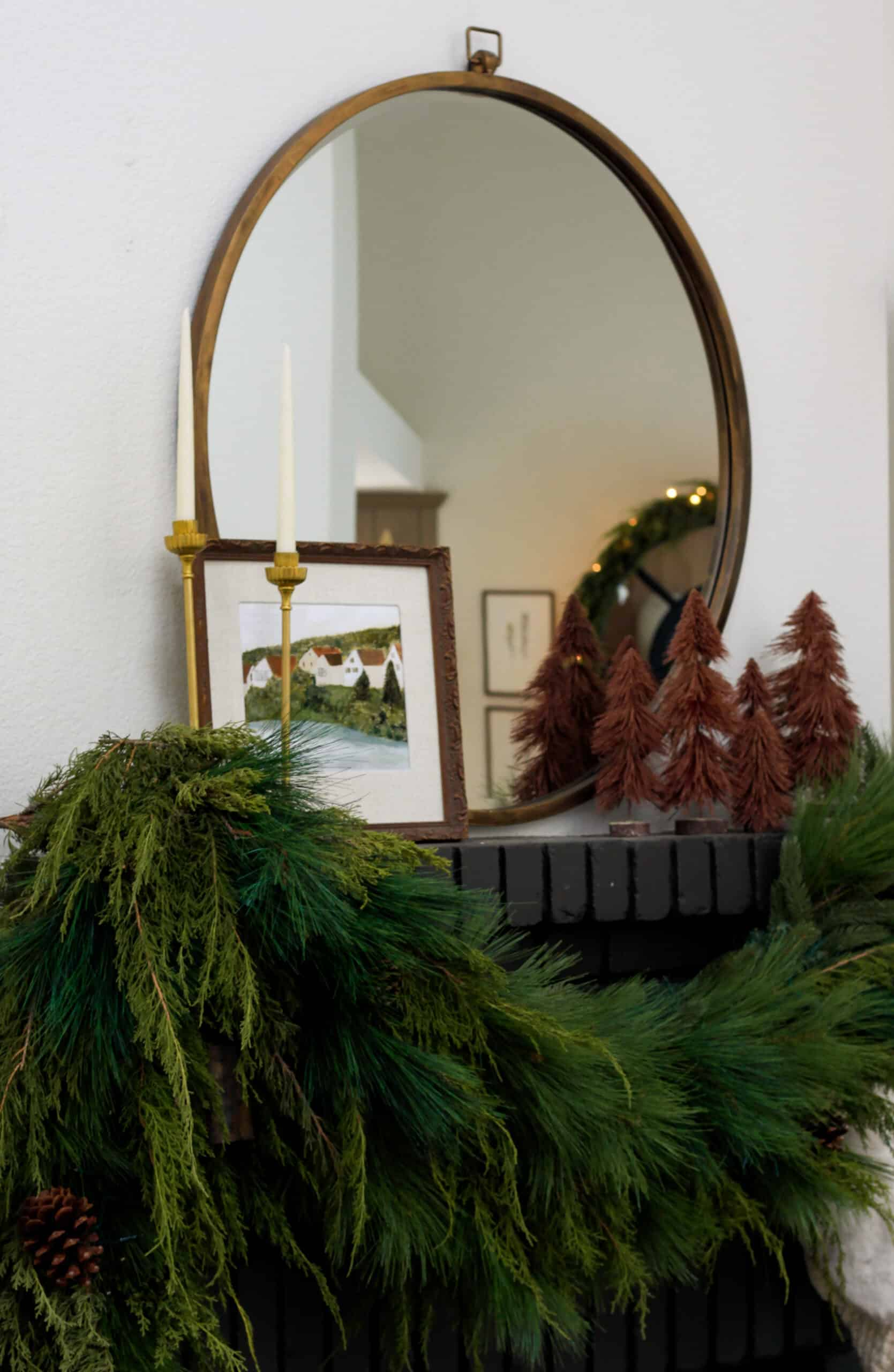 Side view of black fireplace with Christmas greenery