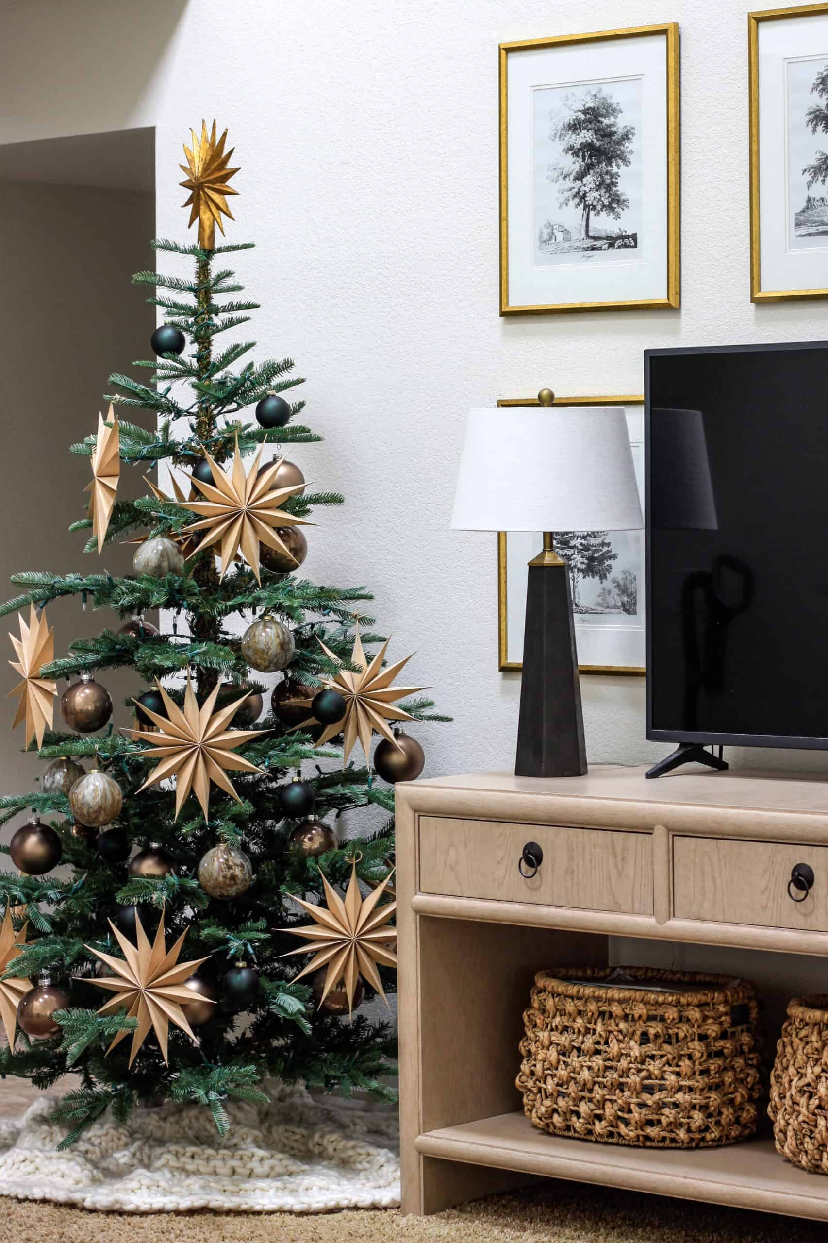 Christmas tree to the left of a TV table