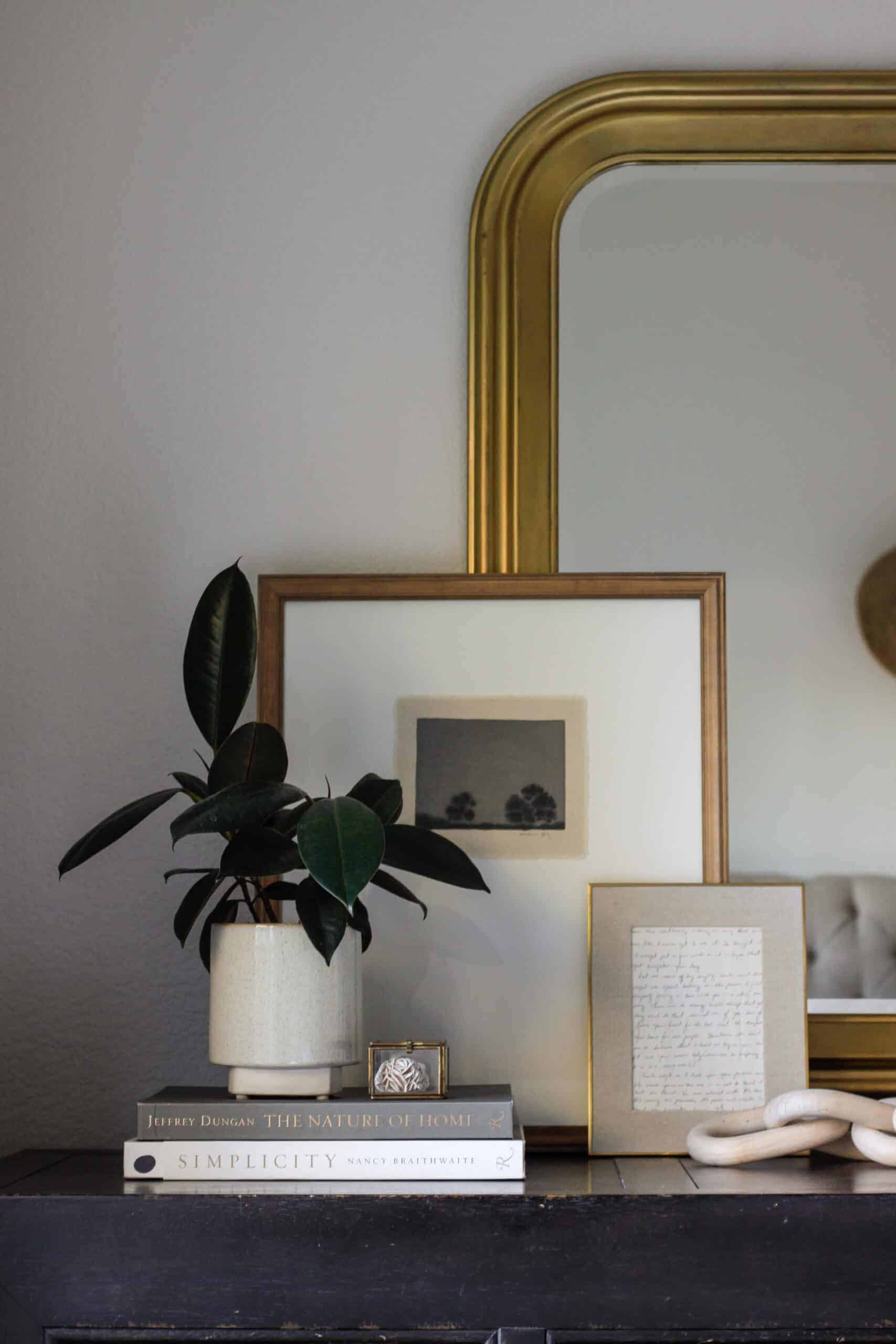 gilded gold mirror with art leaning on it