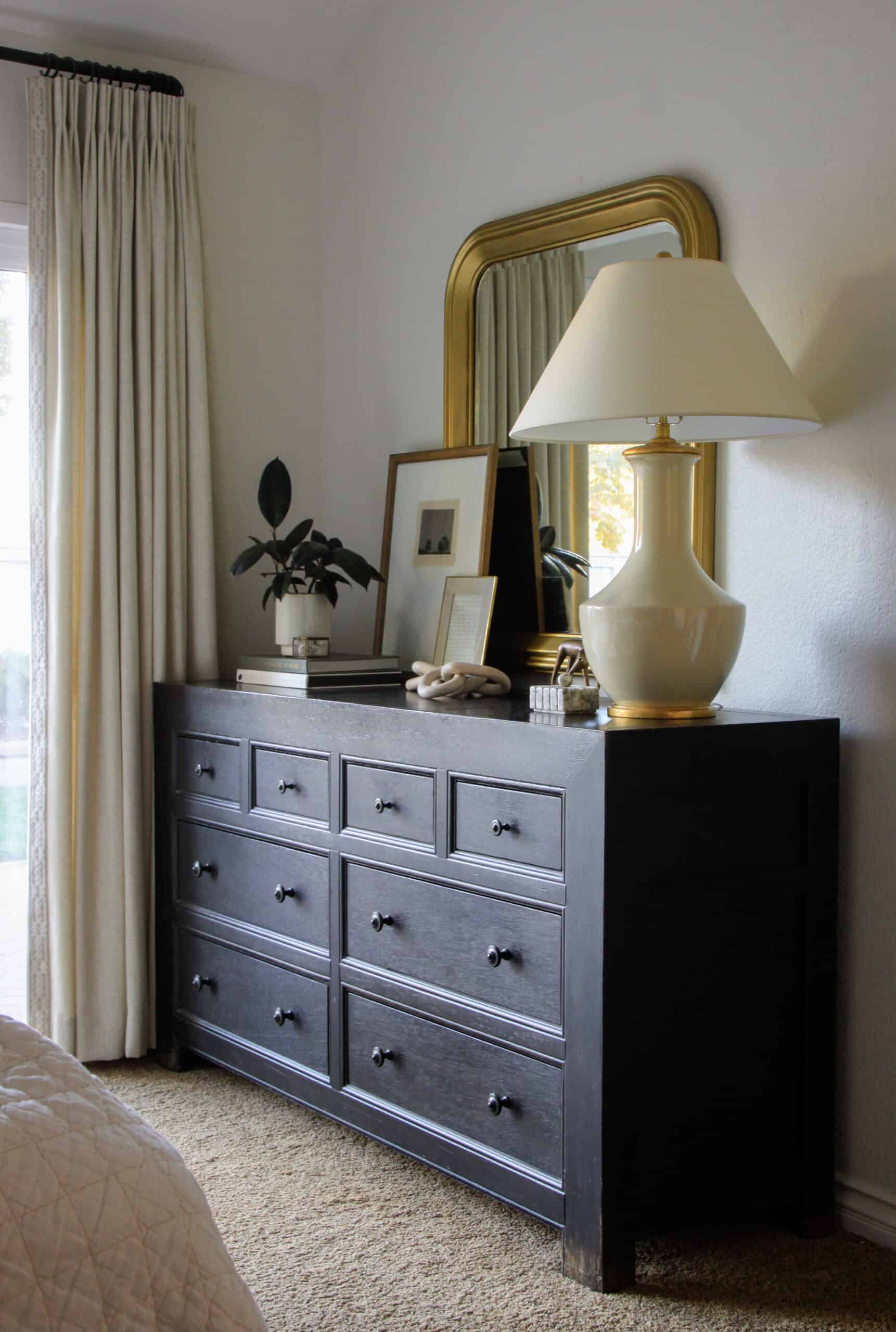 black dresser with gilded mirror above